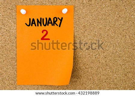 2 JANUARY written on orange paper note pinned on cork board with white thumbtacks, copy space available - stock photo