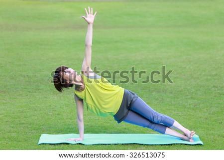 "Japanese Woman Doing YOGA ""Side Plank pose"" - stock photo"
