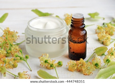 Jar of white cosmetic facial cream, essential oil bottle, linden (tilia) blossom flowers. Holistic herbal skincare.  - stock photo