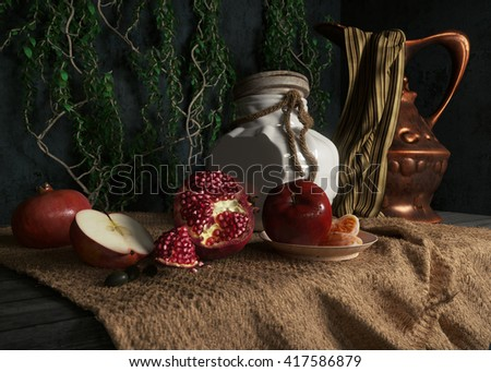 jar, rop, apples,pomegranate,plant and orange on canvas drapery conceptual still-life - stock photo