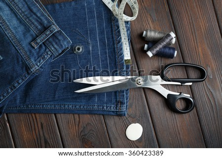 Jeans with dressmaking sewing utensils needlework on the dark old wood background - stock photo