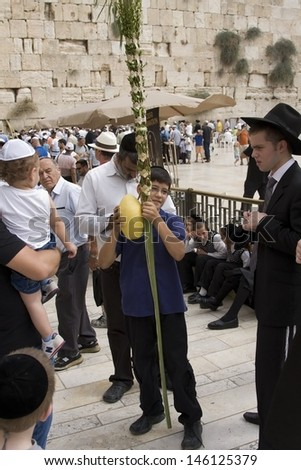 JERUSALEM-October 02: The Jews  at the Western Wall during Jewish holiday of Sukkot, October 2, 2012 in Jerusalem, Israel.Etrog and Lulav is two of four species used during of Sukkot.