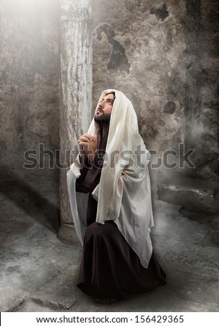 Jesus kneel in prayer toward the light. - stock photo
