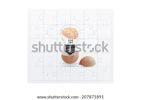 jigsaw concept of brain inside a light bulb an egg cracking open on white background with clipping path  - stock photo