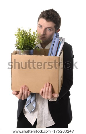 Jobless young Business Man in messy Suit and Necktie carrying Cardboard Box with office belongings Fired from Job isolated on White Background looking depressed, sad an in stress