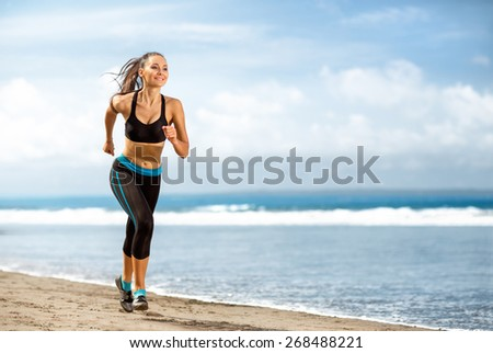 Jogging athlete woman running at sunny beach. Fitness runner girl training outside by the ocean sea in full body length in summer - stock photo