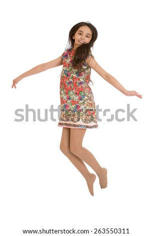 Joyful girl in colorful dress jumps - isolated on white background - stock photo