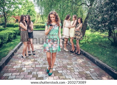 joyful girl with the mobile phone and group of envying girls - stock photo