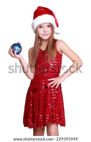 joyful little girl with long blond hair in Santa hat holding christmas ball isolated on white on Holiday theme/Caucasian santa little girl holding blue ball for Christmas decoration - stock photo