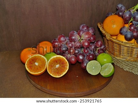 juicy fruit - red grape, lime and red oranges - stock photo