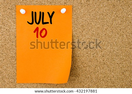 10 JULY written on orange paper note pinned on cork board with white thumbtacks, copy space available - stock photo