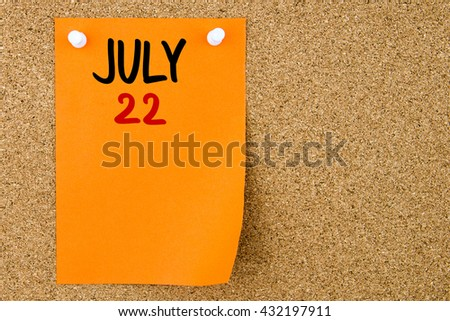 22 JULY written on orange paper note pinned on cork board with white thumbtacks, copy space available - stock photo