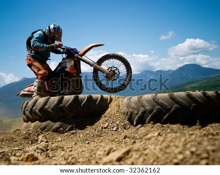 2009, June, Crimea: Enduro competition - off-road motorbike crossing rider surmounts obstacle against a mountains - stock photo