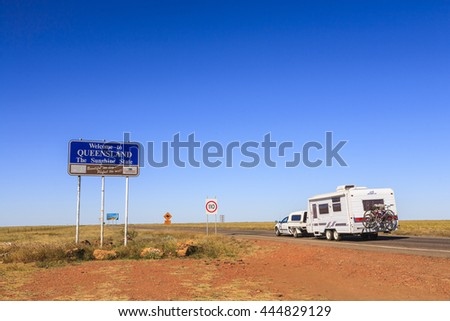 20 June 2006: Queensland, Australia - Welcome to Queensland sign at state border between NT and QLD. Also caravan pulled by ute driving into Queensland, bikes on back.