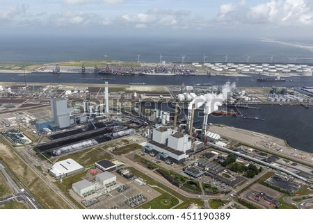 29 June 2016, Rotterdam, Holland. Aerial view of two powerplants in the harbor Maasvlakte with smoke coming out of the chimneys. A clear horizon and a blue sky with some cumulus clouds.