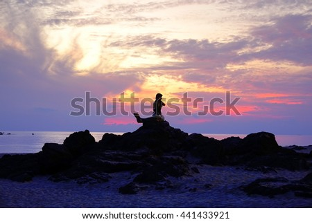 23 June 2016 Songkhla Southern Thailand:Silhouette statue with stone on the beach on sky before sunrise time ove sea background:select focus with shallow depth of field.