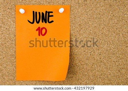 10 JUNE written on orange paper note pinned on cork board with white thumbtacks, copy space available - stock photo