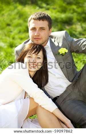 just married in a flowering garden sitting on the grass - stock photo