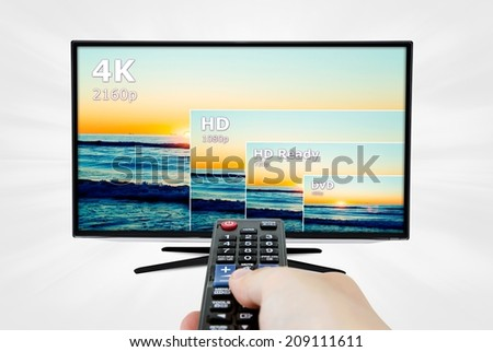4K television display with comparison of resolutions. Remote control in hand - stock photo