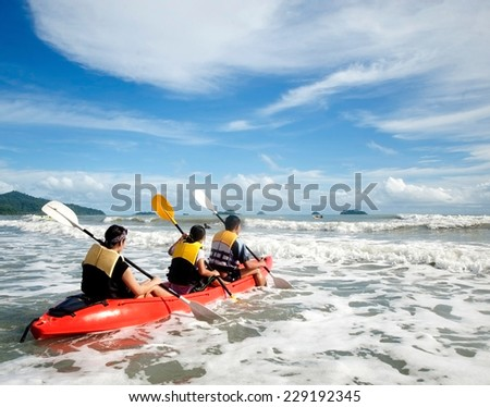 Kayaking. Young is sailing on a sea kayak. Sports and recreation on the water.