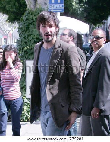 Keanu Reeves looking more like a homeless person than a movie star, smoking after lunch at the Ivy, West Hollywood, Ca, 06/23/04 - stock photo