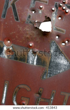 """keep right"" sign, rusting and laden with bullet holes - stock photo"