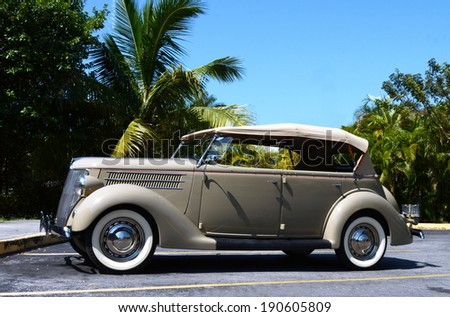 KEY WEST, FL-APRIL 27: A beige 1936 Ford Touring Phaeton Convertible Sedan automobile, side view, in parking lot in Key West, Florida on April 27, 2014.  - stock photo
