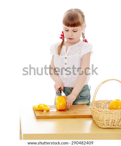 Kid cut with a knife peppers on a wooden Board- isolated on white background - stock photo