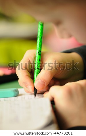 Kid in classroom with pen in hand - stock photo
