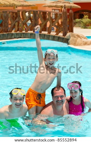 Kids and father in pool - stock photo