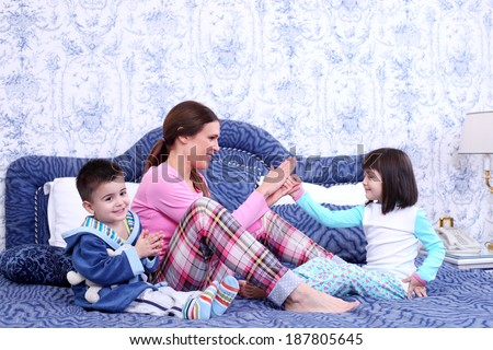 kids and mom play in  bedroom - stock photo