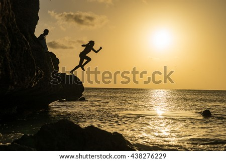 Kids cliff jumping in the sunset - Curacao views a small Caribbean Island in the Dutch Antilles - stock photo