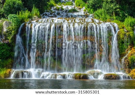 2 kilometers long promenade leading through gardens of imperial palace in caserta is decorated by many fountains and statues from bernini and ends by artificial waterfall. - stock photo