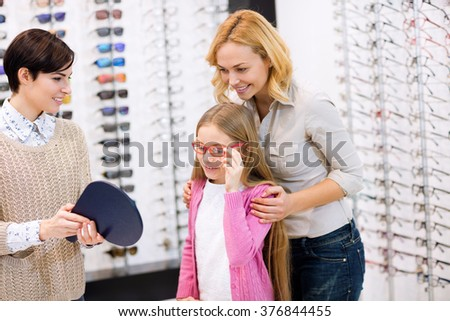 Kind saleswoman hold mirror while child try frames for eyeglasses - stock photo