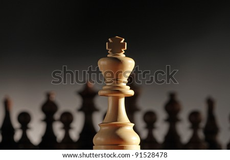 king chess piece with others in background. Low depth of field, focus on foreground. - stock photo