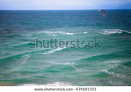 kite surfer surfing, extreme water sport - stock photo