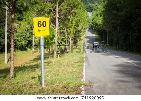 60 Km per hour traffic sign post on mountain road with moving car with pine forest view