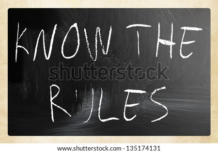 """Know the rules"" handwritten with white chalk on a blackboard."
