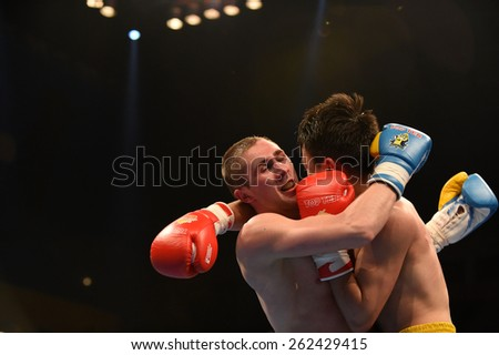 Kyiv, UKRAINE - March 20, 2015 : PRUDKYI Oleg (UA) and SHAN Jun (China)  in the ring during boxing fight Ukraine Otamans vs China Dragons in Palace of Sport in Kiev, Ukraine