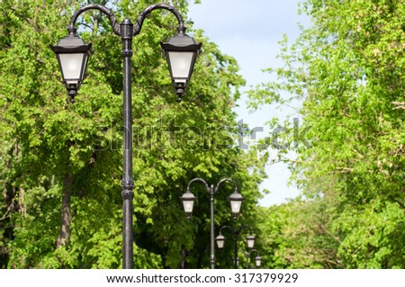 lamps in the Park alley in the spring - stock photo
