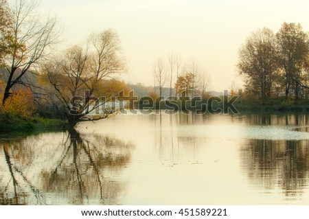 Landscape. Sunset over the lake, fall trees reflected in water.  Water Lake District Sokolki Tatarstan Russia