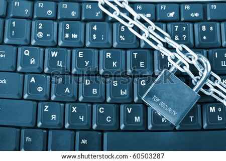 laptop keyboard secured with chain and padlock - stock photo