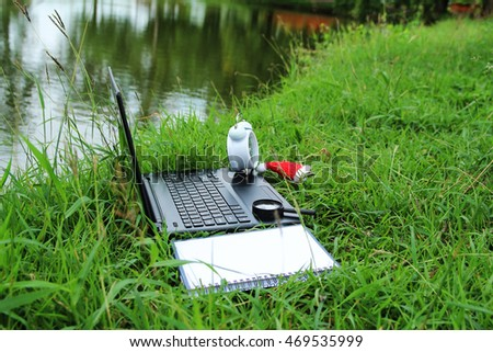laptop on green grass at park