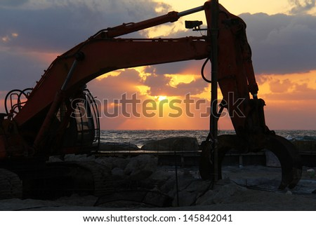 Large excavator on the sunset  over sea background - stock photo