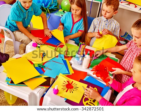 Large Group kids holding colored paper on table in kindergarten .  - stock photo