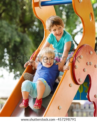laughing children on slide at playground area  in summer