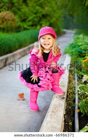 laughing fashionable little girl walking in park - stock photo