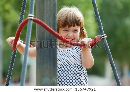 laughing girl climbing at ropes on playground area