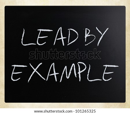 """""""Lead by example"""" handwritten with white chalk on a blackboard. - stock photo"""