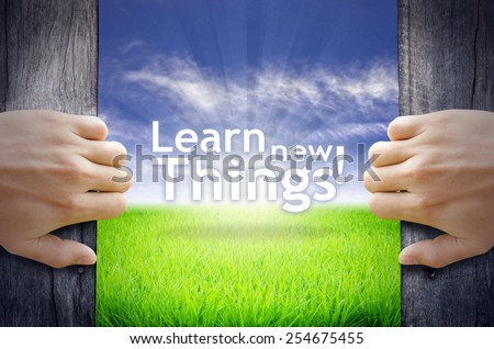 """""""Learn new Things"""" Motivational quotes. Hands opening a wooden door then found a texts floating among new world as green grass field, Blue sky and the Sunrise. - stock photo"""